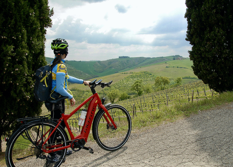 Stefania con bici guarda paesaggio toscana